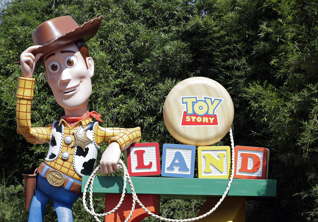 In this Saturday, June 23, 2018 photo, a statue of the character Sheriff Woody greets visitors at the entrance Toy Story Land in Disney's Hollywood Studios at Walt Disney World in Lake Buena Vista ...