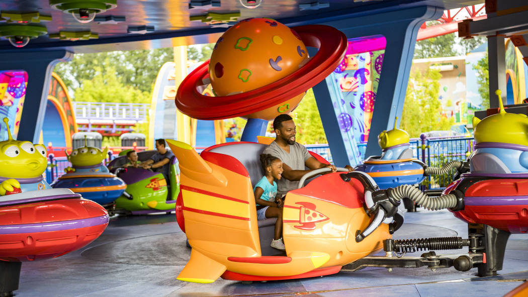 Little green Aliens from Pixar Animation StudiosՠToy Story films pilot toy rocket ships in the Alien Swirling Saucers attraction in Toy Story Land at Disney's Hollywood Studios. (Matt Stroshane, ...