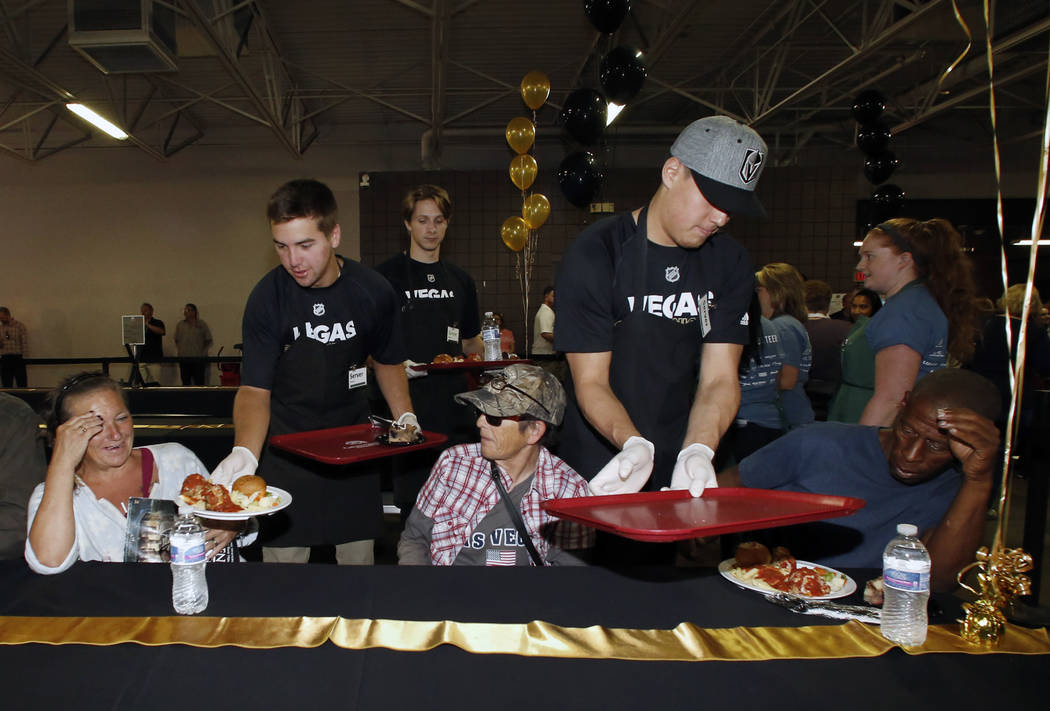 The Vegas Golden Knights prospects Jack Dugan, left, and Zach Whitecloud serve a special free community meal to clients at Catholic Charities of Southern Nevada on Monday, June 25, 2018, in Las Ve ...