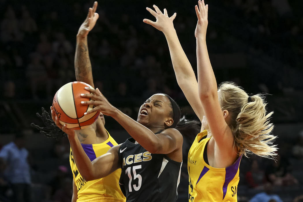 Las Vegas Aces guard Lindsay Allen (15), center, goes up for a shot against Los Angeles Sparks guard Riquna Williams (2), left, and Sparks forward Karlie Samuelson (44) during the first half of a ...