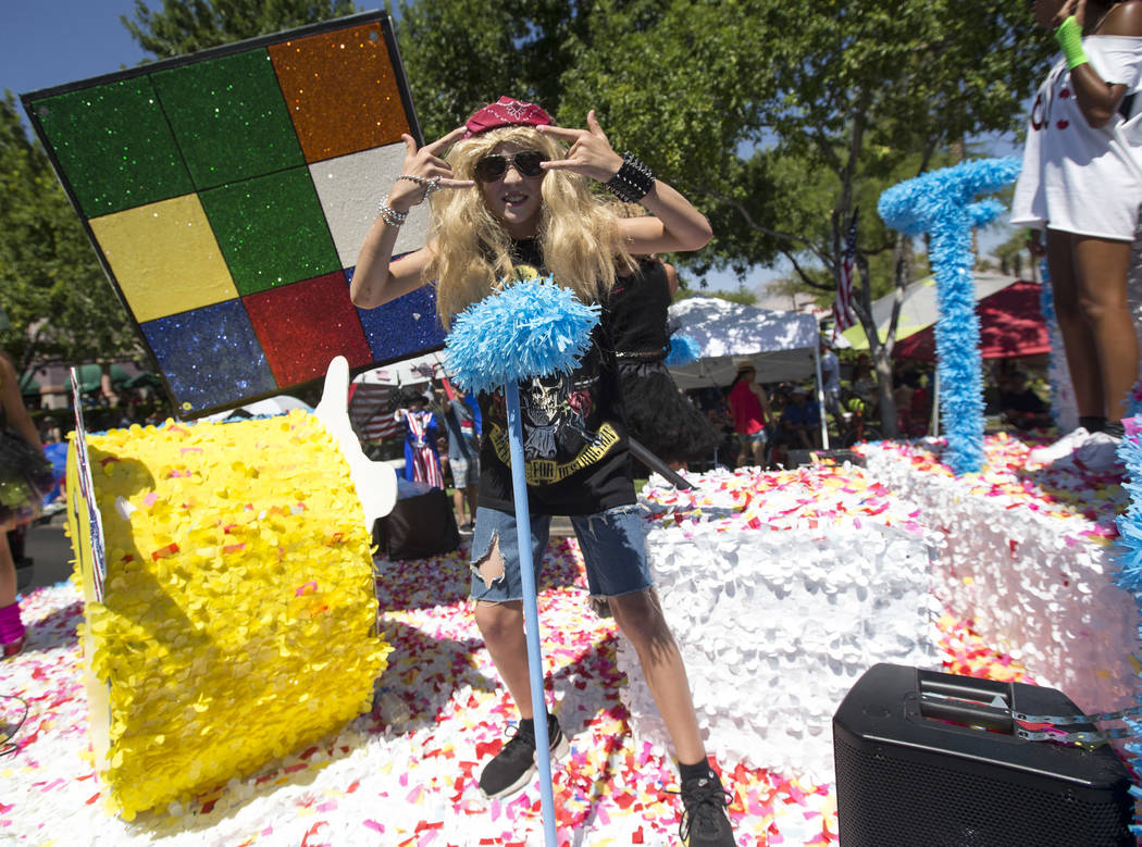 """A youngster in character dances on the Howard Hughes Corporation's """"80's Flashback Kids in America""""float during the Summerlin Council Patriotic Parade in Las Vegas on Wednesday, Ju ..."""