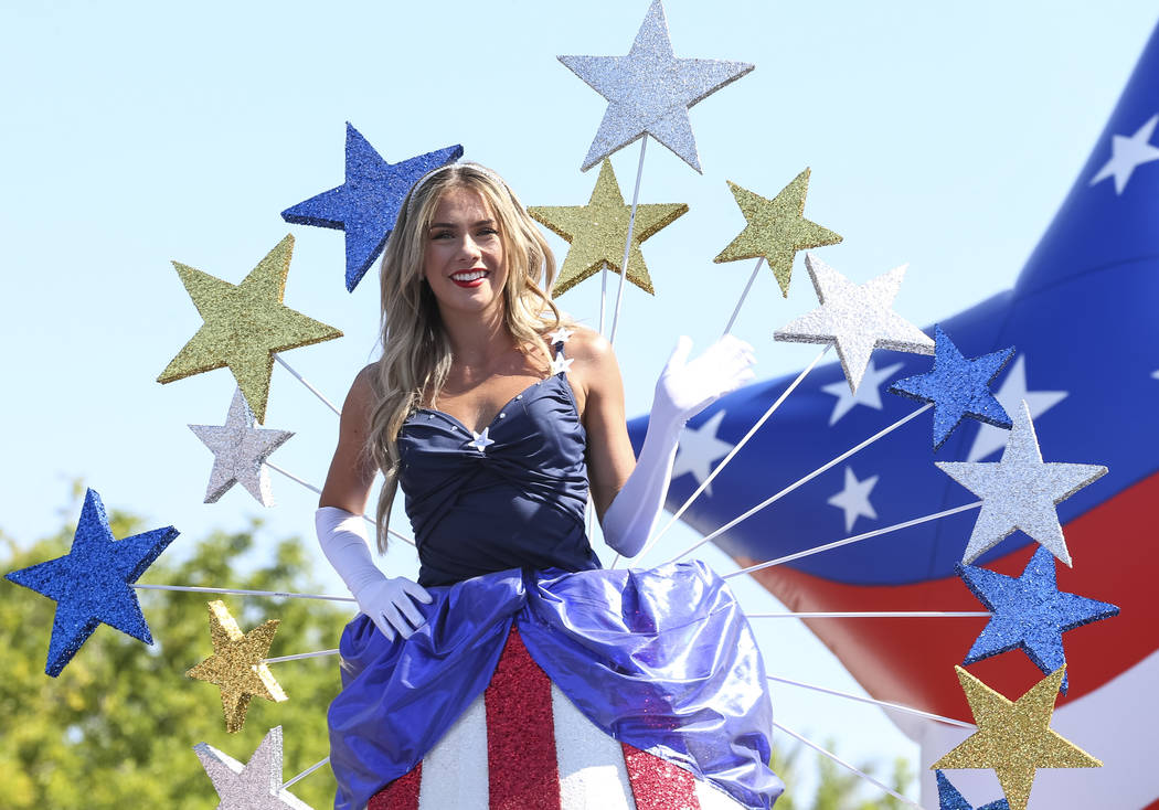 """A participant riding the Pardee Homes """"America Standing Tall"""" float waves to people in the crowd during the Summerlin Council Patriotic Parade in Las Vegas on Wednesday, July 4, 2018. Ri ..."""
