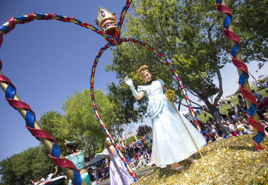 """Participants riding the Red Rock Fertility """"Dream Big with the Princess"""" float wave to people in the crowd during the Summerlin Council Patriotic Parade in Las Vegas on Wednesday, July 4 ..."""