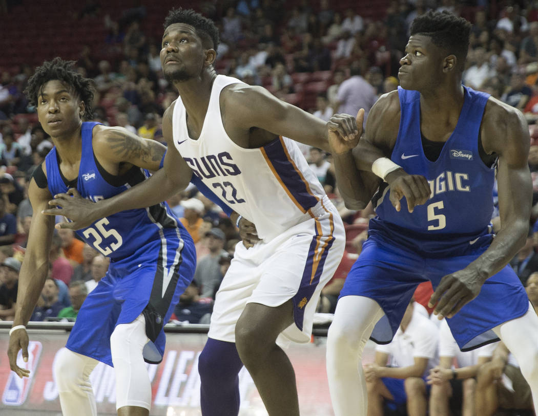 Phoenix Suns center Deandre Ayton (22) fights for a rebound with Orlando Magic forward Wesley Iwundu (25) and center Mohamed Bamba (5) in the third quarter during the NBA Summer League on Monday, ...