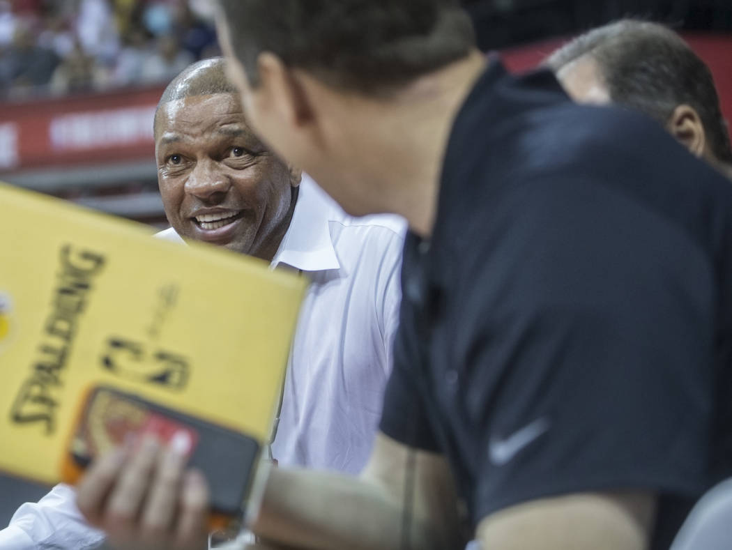 Los Angeles Clippers coach Doc Rivers, left, watches the Philadelphia 76ers NBA Summer League game with the Phoenix Suns on Thursday, July 12, 2018, at the Thomas & Mack Center, in Las Vegas. ...