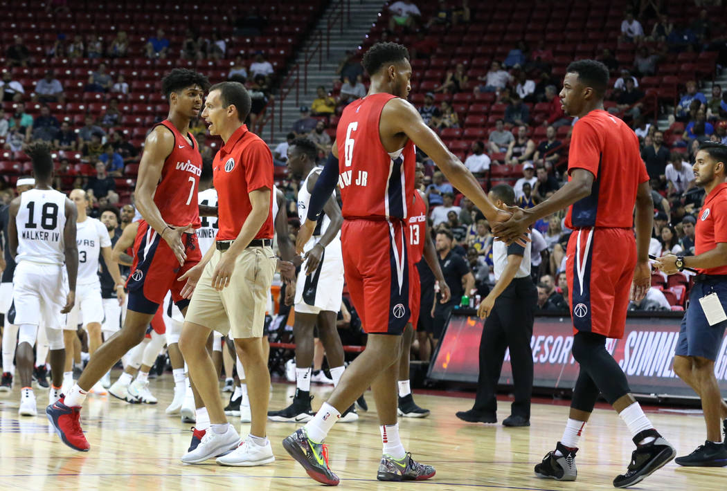 Washington Wizards' forward Devin Robinson (7) and guard Troy Brown (6) leave the court as Wizards' Summer League head coach Ryan Richman calls a timeout during an NBA Summer League basketball gam ...