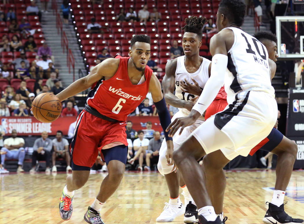 Washington Wizards' guard Troy Brown (6) tries to drive past the San Antonio Spurs' guard Lonnie Walker IV, center, and forward Chimezie Metu (10) during an NBA Summer League basketball game at th ...