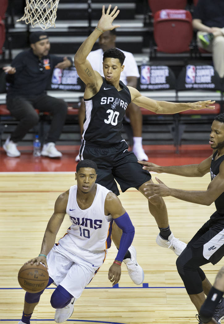 San Antonio Spurs guard Jordan Green (30) leaps to block the shot of Phoenix Suns guard Shaquille Harrison (10) in the first quarter during the NBA Summer League on Friday, July 13, 2018 ...