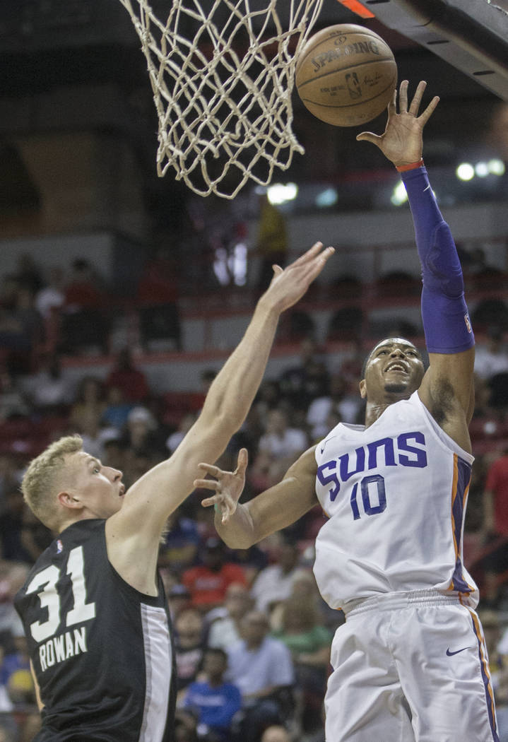 Phoenix Suns guard Shaquille Harrison (10) drives past San Antonio Spurs guard Maverick Rowan (31) in the second quarter during theNBA Summer Leagueon Friday, July 13, 2018, at the Tho ...