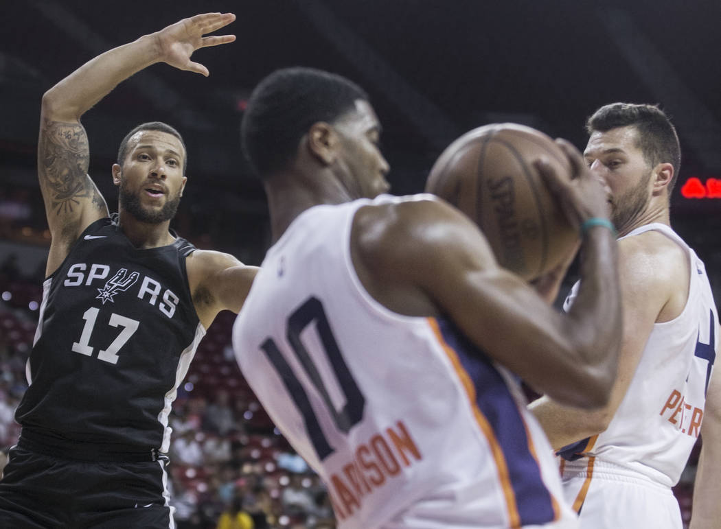 San Antonio Spurs guard Trey McKinney-Jones (17) fights for a rebound with Phoenix Suns guard Shaquille Harrison (10) and forward Alec Peters (14) in the fourth quarter during the NBA Summer ...