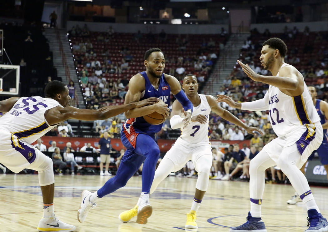 The Detroit Pistons guard Bruce Brown, center, drives past the Los Angeles Lakers forward Nick King (55) Demarcus Holland (7) and Jeff Ayres (12) during an NBA Summer League basketball game at the ...