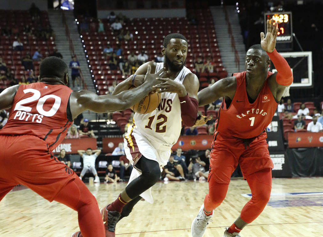 The Cleveland Cavaliers guard Scoochi Smith (12) drives past between the Toronto Raptors guard Rawle Alkins (1) and Giddy Potts (20) during an NBA Summer League basketball game at the Thomas and M ...