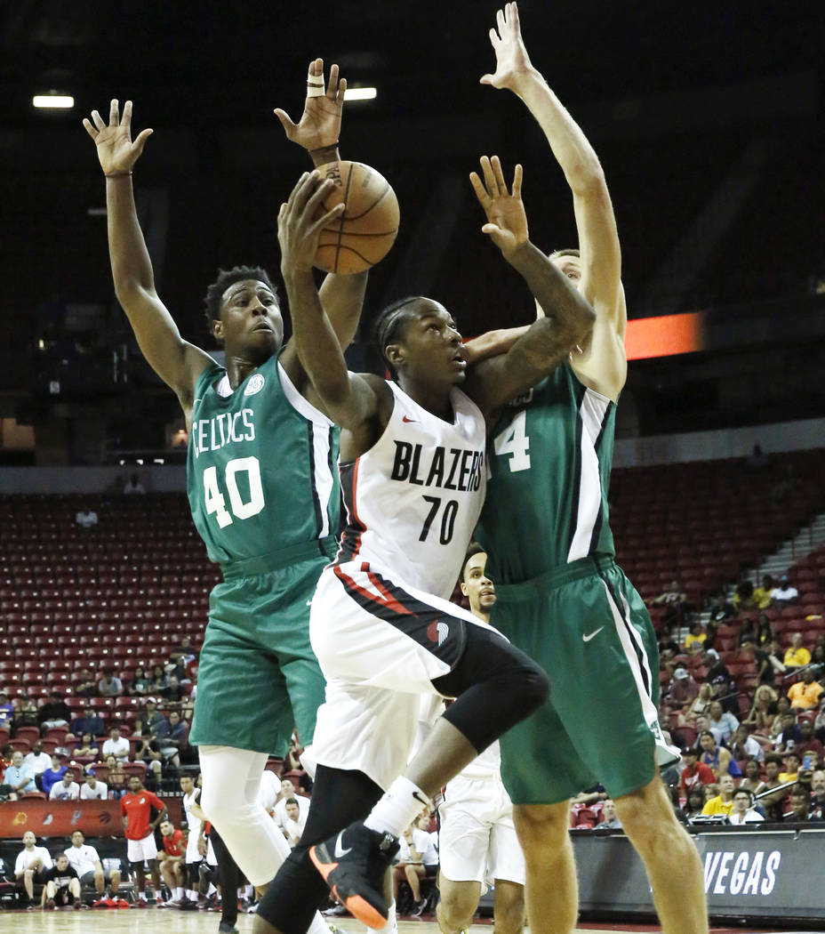 The Portland Trail Blazers Archie Goodwin (70) tries to shoot around the Boston Celtics Justin Gibbs (40) and forward Jarrod Uthoff (64) during an NBA Summer League basketball game at the Thomas a ...