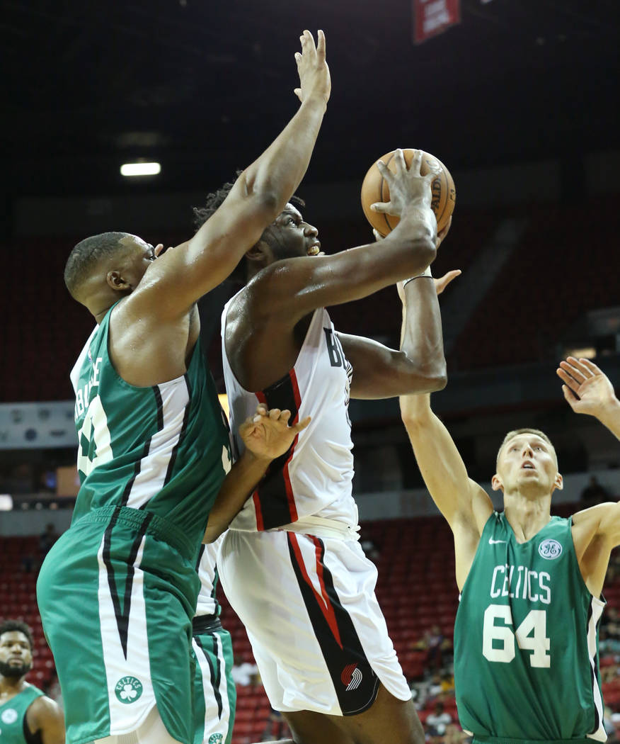 The Portland Trail Blazers forward Caleb Swanigan (50) tries to shoot around the Boston Celtics center Guerschon Yabusele (30) and forward Jarrod Uthoff (64) during an NBA Summer League basketball ...