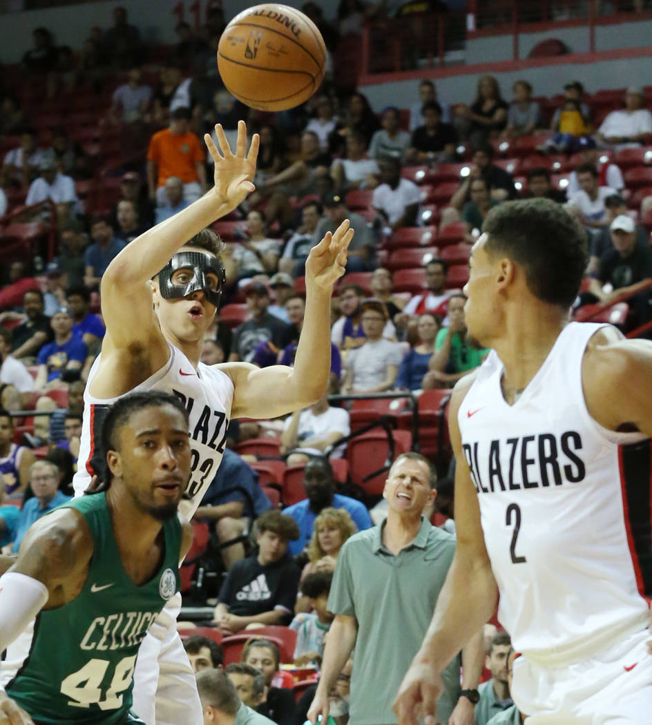 The Portland Trail Blazers center Zach Collins (33) passes the ball guard to Wade Baldwin IV (2) over the Boston Celtics Trey Davis, center, during an NBA Summer League basketball game at the Thom ...