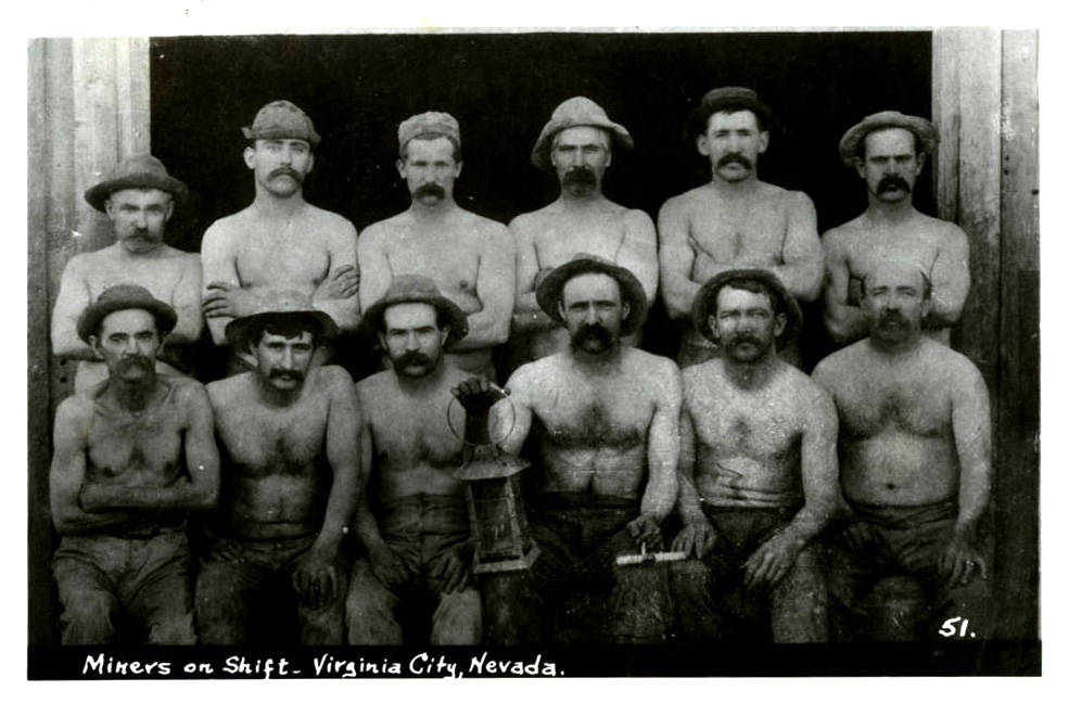 "A group photograph of unidentified miners on shift in Virginia City, Nevada. Printed on the front of the card: ""Miners on shift - Virginia City, Nevada."" Original Collection Fred and Maurine Wi ..."