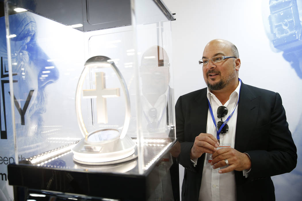 Anthony Zuiker, creator of CSI television shows and founder of Divinity, talks about his collection of crosses on display during the International Cemetery, Cremation, and Funeral Association conv ...