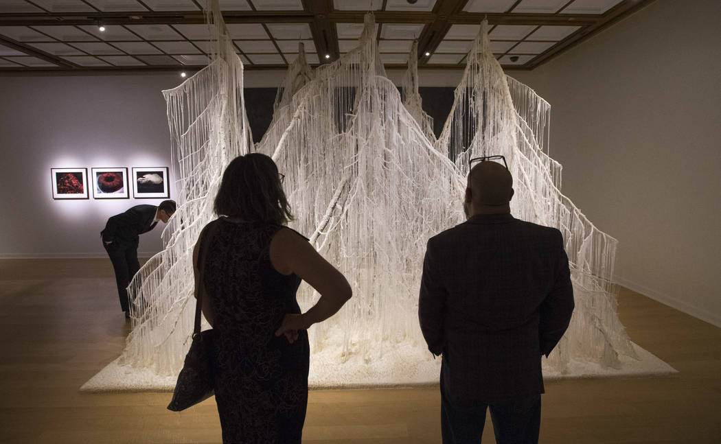 "People look over ""Vertical Emptiness"" an installation by Japanese artist Yasuaki Onishi during the Primal Water exhibition at the Bellagio Gallery of Fine Art in Las Vegas on Thursday, J ..."