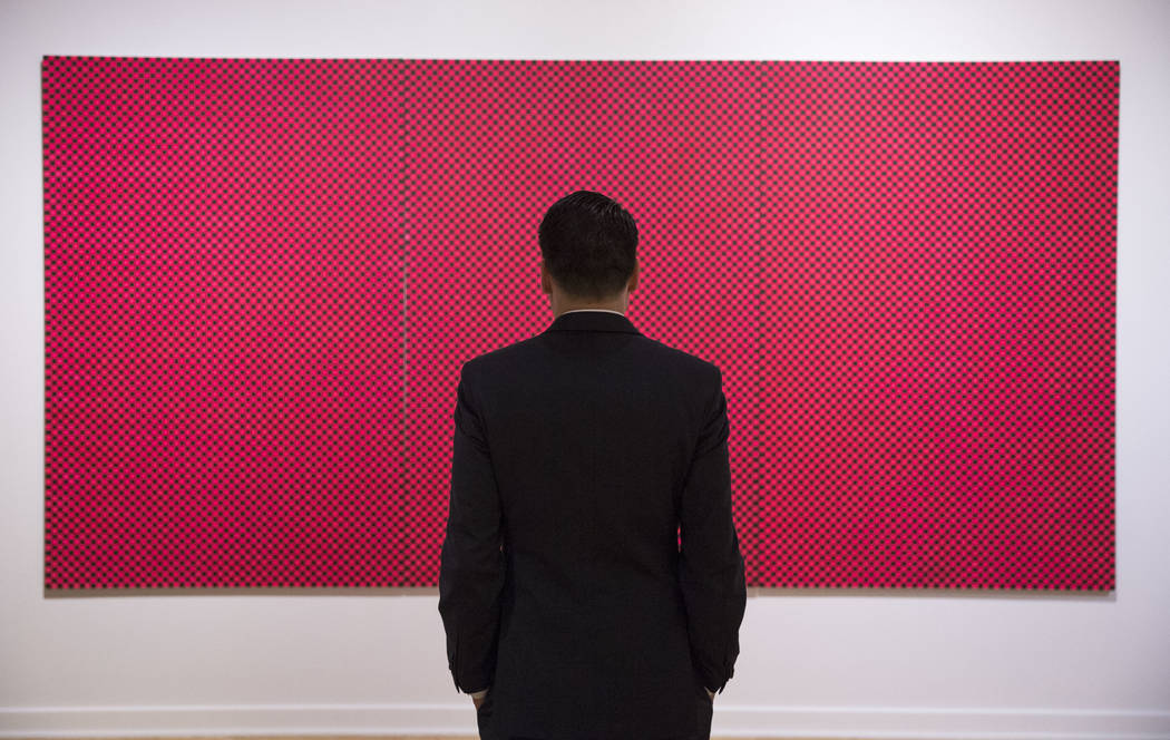 """A man looks at """"Infinity Nets"""" an acrylic on canvas by Japanese artist Yayoi Kusama during the Primal Water exhibition at the Bellagio Gallery of Fine Art in Las Vegas on Thursday, June ..."""