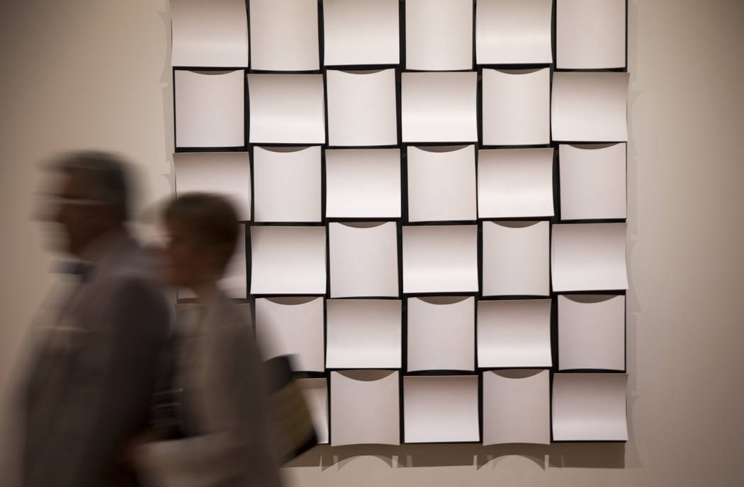 """A couple walks past """"APPARATUS"""" by Japanese artist Motonao Takasaki on display during the Primal Water exhibition at the Bellagio Gallery of Fine Art in Las Vegas on Thursday, June 28, 2 ..."""