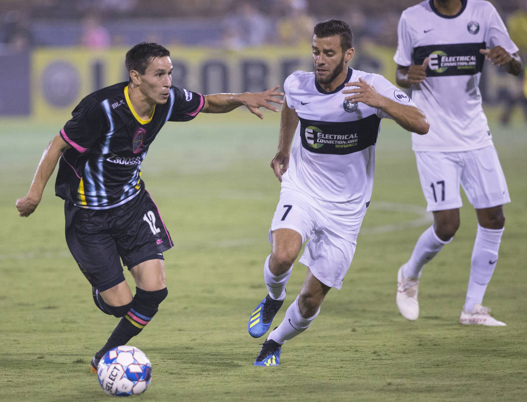 Las Vegas Lights FC midfielder Eric Avila (12) pushes the ball up field past Saint Louis FC midfielder Joey Calistri (7) in the first half on Saturday, July 7, 2018, at Cashman Field, in Las Vegas ...