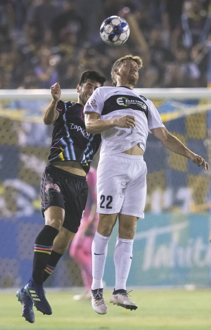 Las Vegas Lights FC defender Nicolas Samayoa (5) goes up for a header against Saint Louis FC forward Kyle Greig (22) in the first half on Saturday, July 7, 2018, at Cashman Field, in Las Vegas. Be ...