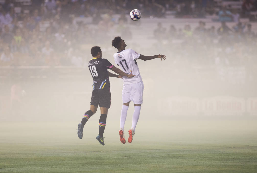 Las Vegas Lights FC midfielder Juan Herrera-Perla (13) goes up for a header with Saint Louis FC midfielder Wal Fall (17) in the first half on Saturday, July 7, 2018, at Cashman Field, in Las Vegas ...