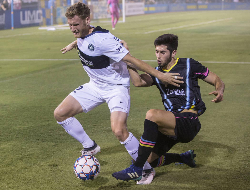 Las Vegas Lights FC defender Nicolas Samayoa (5) fights for a ball with Saint Louis FC forward Kyle Greig (22) in the first half on Saturday, July 7, 2018, at Cashman Field, in Las Vegas. Benjami ...
