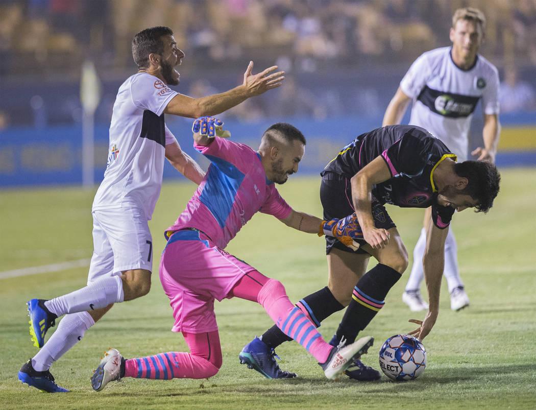 Las Vegas Lights FC goalkeeper Ricardo Ferriño (1) and defender Nicolas Samayoa (5) clear a ball in traffic against Saint Louis FC midfielder Joey Calistri (7) in the first half on Saturday, ...