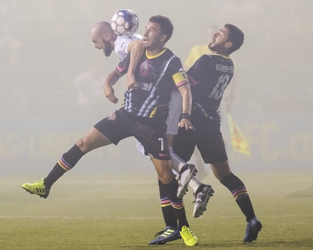 Las Vegas Lights FC midfielder's Carlos Alvarez (7) and Juan Herrera-Perla (13) fight for a ball with Saint Louis FC defender Kyle Culbertson (5) in the first half on Saturday, July 7, 2018, at Ca ...