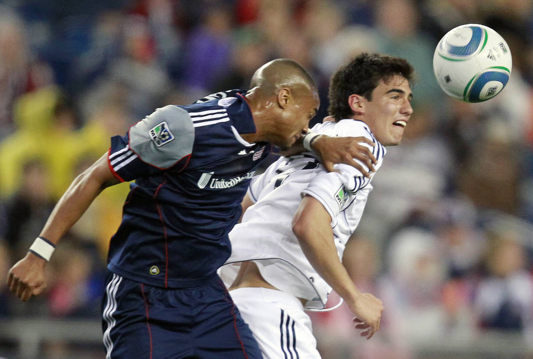 New England Revolutions' Darrius Barnes, left, and Vancouver Whitecaps' Omar Salgado try to get a head on the ball in the first half of an MLS soccer game, Saturday, May 14, 2011, in Foxborough, M ...