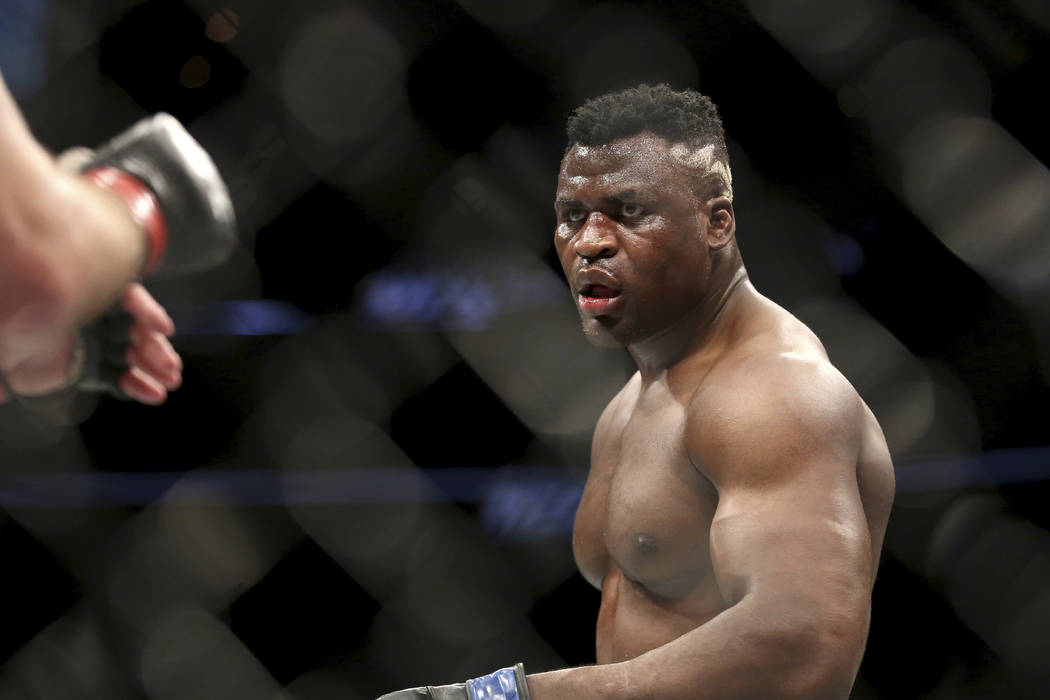 Francis Ngannou in action against Stipe Miocic during a heavyweight championship mixed martial arts bout at UFC 220, Sunday, Jan. 21, 2018, in Boston. Miocic retained his title via unanimous decis ...