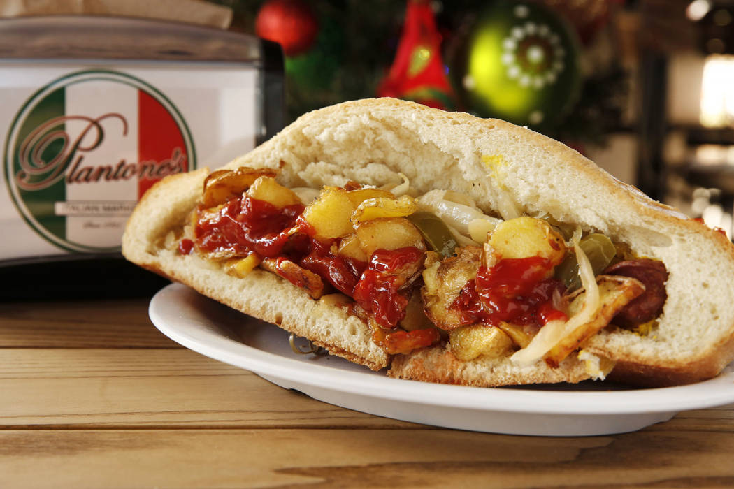 The Italian Hot Dog features a hollowed out Italian sub roll stuffed with mustard, two split hot dogs, sauted onions and green peppers, and fried potato squares topped with ketchup at Plantone's ...