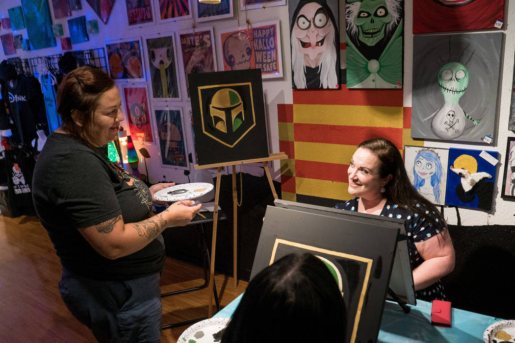 Leslie Ann Farrell, art instructor and owner of The Bubblegum Gallery, speaks with attendee Tammy Wilkins, right, at the Boba Fett Golden Knight Paint Class at the Bubblegum Gallery in Las Vegas, ...