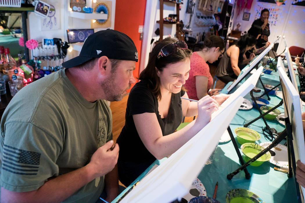 Samuel Jernigan, left, and girlfriend Calin Elardi, right, attend the Boba Fett Golden Knight Paint Class at The Bubblegum Gallery in Las Vegas, Friday, June 29, 2018. (Marcus Villagran/Las Vegas ...