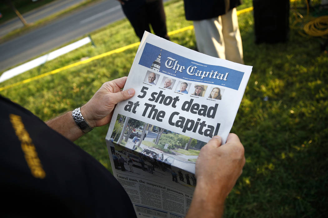 Steve Schuh, county executive of Anne Arundel County, holds a copy of The Capital Gazette near the scene of a shooting at the newspaper's office, Friday, June 29, 2018, in Annapolis, Md. A man arm ...