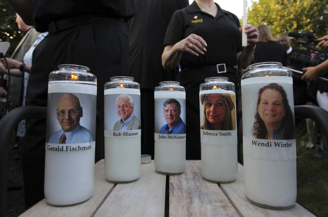 Photos of five journalists adorn candles during a vigil across the street from where they were slain in their newsroom in Annapolis, Md., Friday, June 29, 2018. Prosecutors say Jarrod W. Ramos op ...