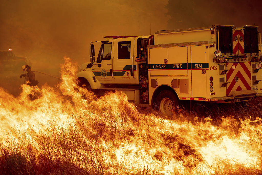 A firefighter scrambles to stop the Pawnee fire as it spots across Highway 20 near Clearlake Oaks, Calif., on Sunday, July 1, 2018. (AP Photo/Noah Berger)