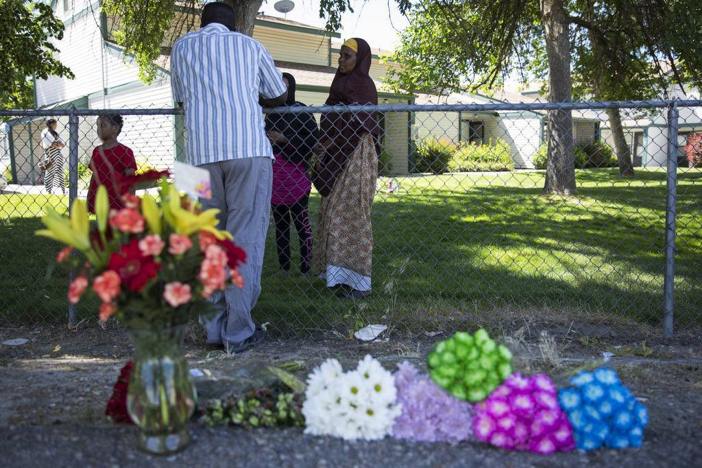 Ibod Hasn, center, talks to a friend who came to visit after Saturday's stabbing attack in Boise, Idaho, Sunday, July 1, 2018. A man who had been asked to leave an Idaho apartment complex because ...