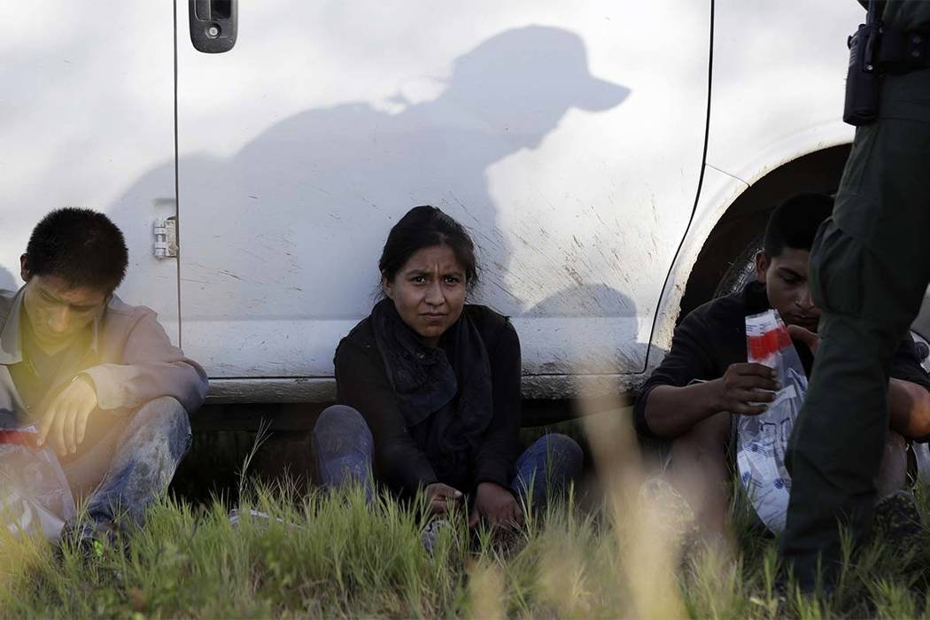 In this Aug. 11, 2017 file photo, immigrants suspected of crossing into the United States illegally along the Rio Grande near Granjeno, Texas, are held by U.S. Customs and Border Patrol agents. (E ...