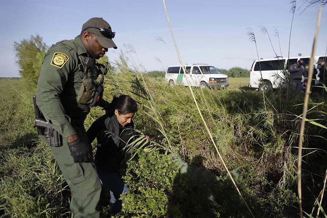 In this Aug. 11, 2017 file photo, a U.S. Customs and Border Patrol agent escorts an immigrant suspected of crossing into the United States illegally along the Rio Grande near Granjeno, Texas. (Eri ...
