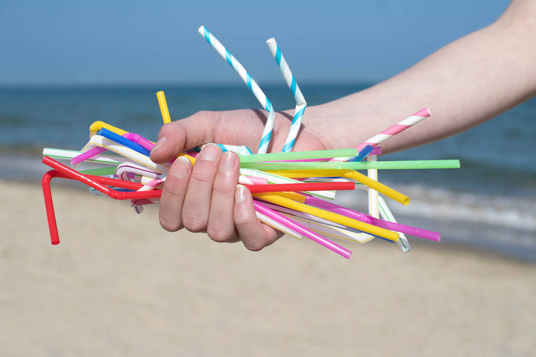 Close Up Of Hand Holding Plastic Straws Polluting Beach (Getty Images)