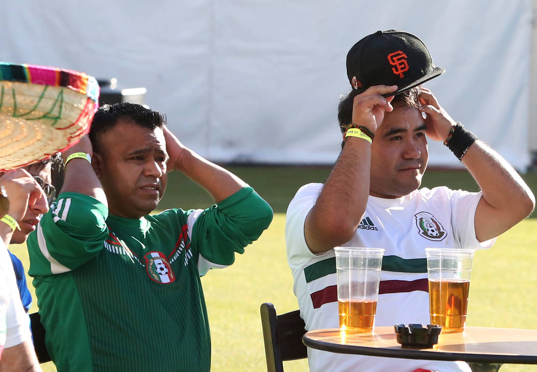 Mexico fans Ismael Matias, left, and Juaquin Dominguez, of Las Vegas react to a play as they watch a match between Mexico and Brazil during a watch party of the World Cup at the Downtown Las Vegas ...