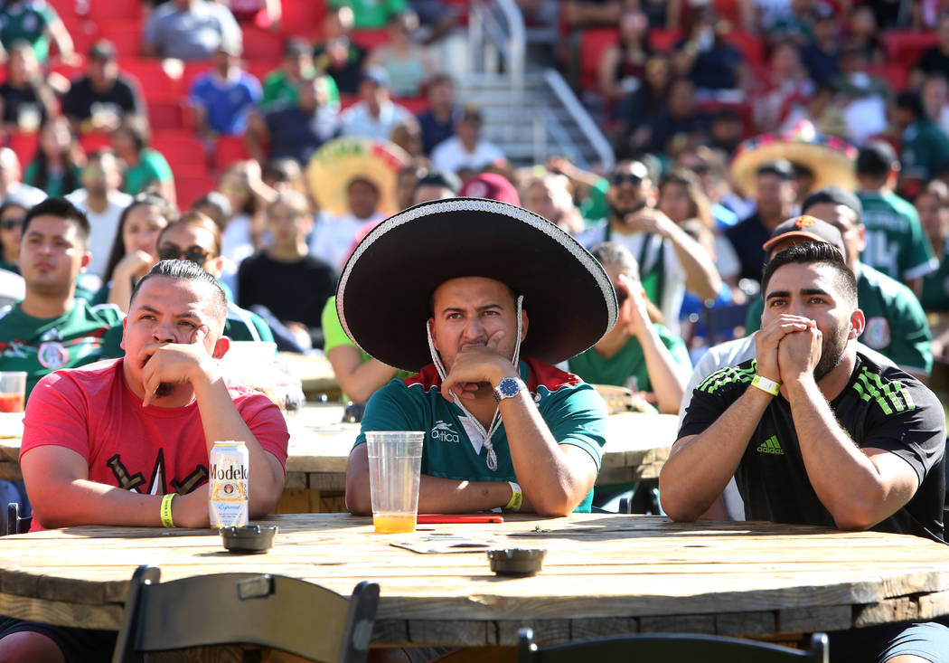 Mexico fans Ivan Urbina, left, Roberto Aguayo, and Edward Gutierrez, right, of Las Vegas watch the last minute of a match between Mexico and Brazil during a watch party of the World Cup at the Dow ...