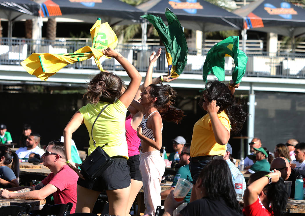Brazil fans Iris Leite of Sao Paulo, Brazil, left, Mayara Marcela Nones, center, and Caroline Ramon, right, both of Rio De Janeiro, Brazil, celebrate during a watch party of the World Cup at the D ...