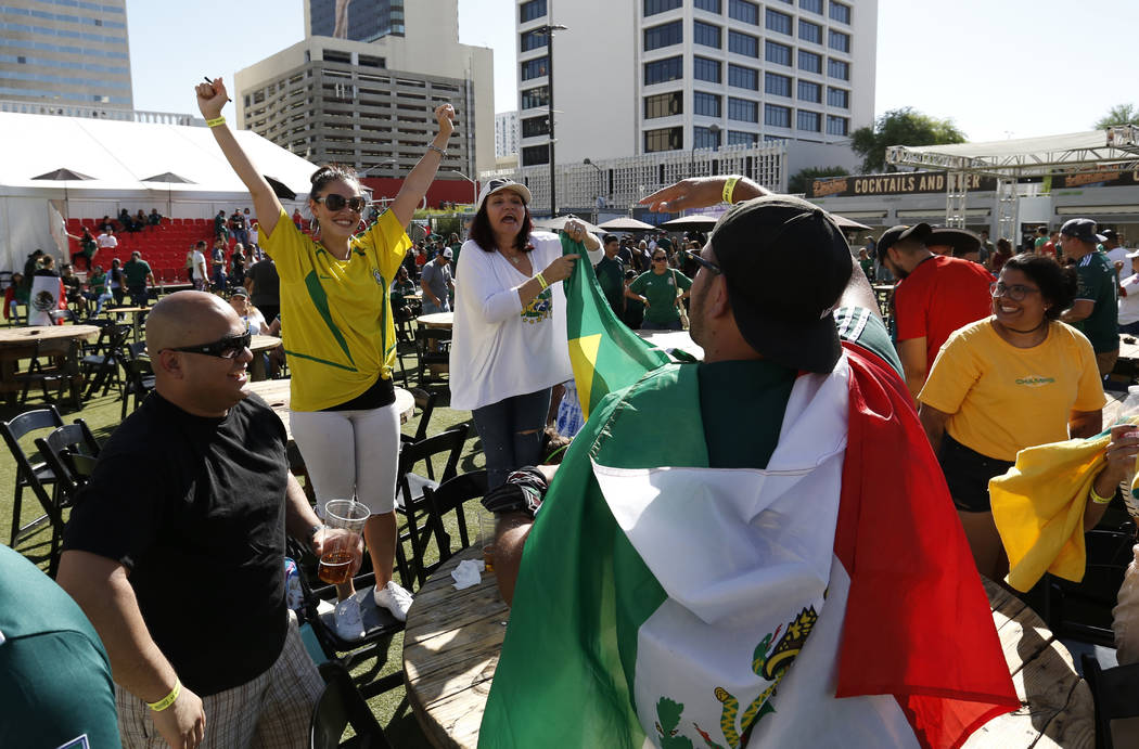 A Mexico fan Rickey Flores of Fresno, Calif., center, congratulates Brazil fans, including Caroline Bale, second left, of Las Vegas as they celebrate their teamÕs victory during a watch party ...