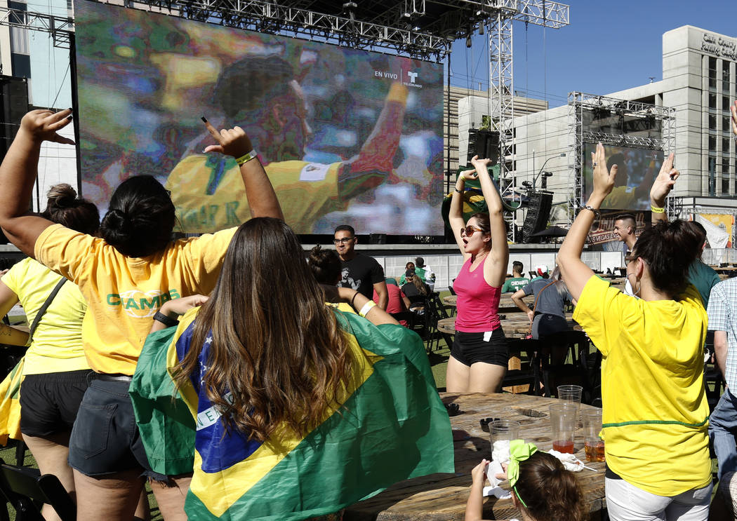 Brazil fans, including Caroline Bale, right, of Las Vegas celebrate during a watch party of the World Cup at the Downtown Las Vegas Event Center after Neymar scores the first goal against Mexico o ...
