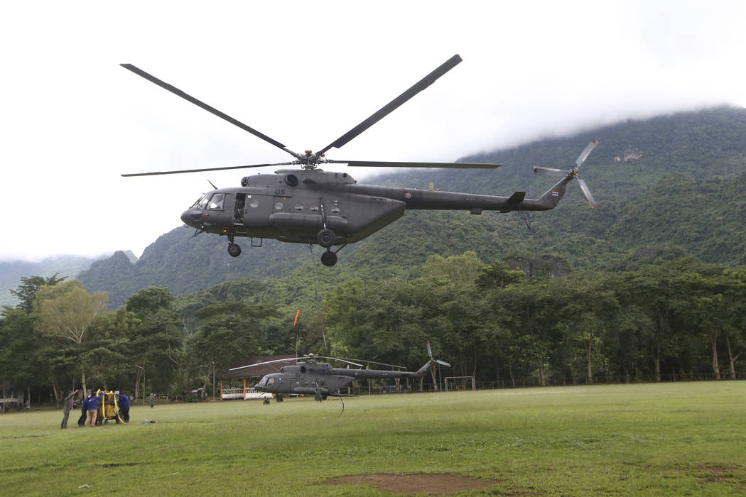 A military transport helicopter prepares to carry drill machine to be used for the search of missing 12 boys and their soccer coach, in Mae Sai, Chiang Rai province, in northern Thailand, Monday, ...