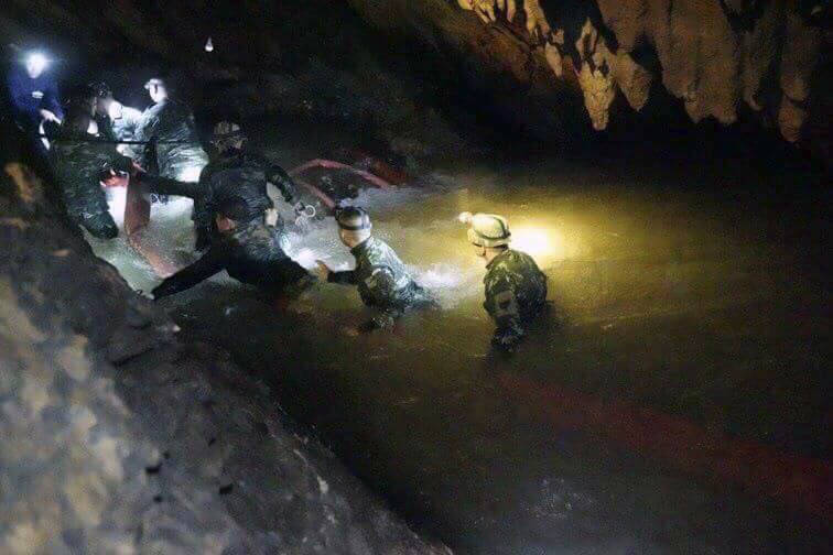 In this handout photo released by Tham Luang Rescue Operation Center, Thai rescue teams walk inside cave complex where 12 boys and their soccer coach went missing, in Mae Sai, Chiang Rai province, ...