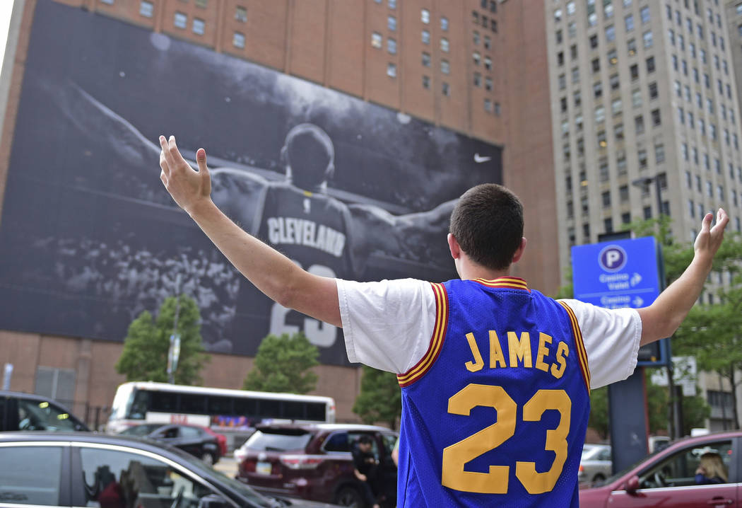 In this June 9, 2017, file photo, Cleveland Cavaliers fan Jordan Phillips poses for a photo in front of a poster featuring Cleveland Cavaliers forward LeBron James, before Game 4 of the basketball ...